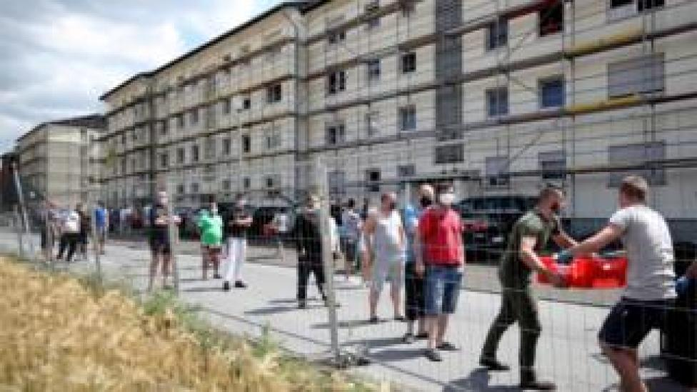 Authorities distribute quarantined food to workers at a meat factory in Tonni