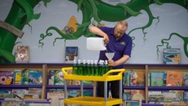 """Site manager Mark Lee fills bottles of hand sanitizer at Queen""""s Hill Primary School in Costessey near Norwich"""
