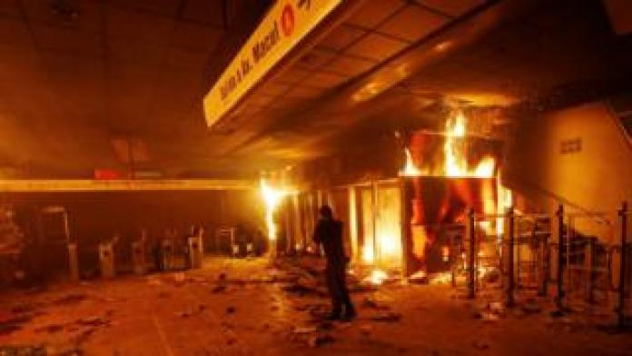 A subway ticket office is seen on fire during a protest against the increase in the subway ticket prices in Santiago