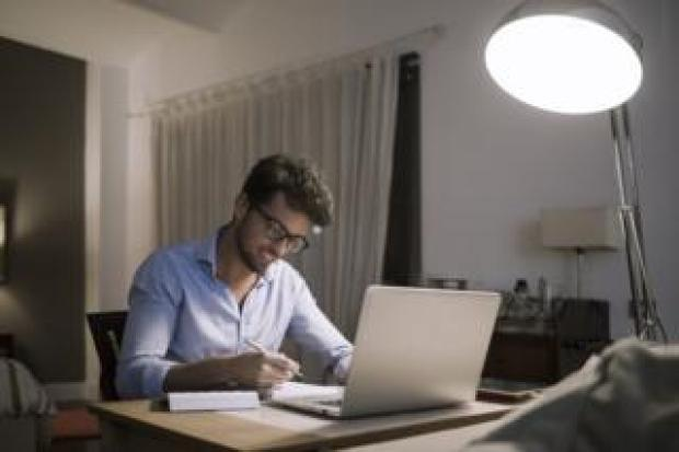 Man working at home with the lights on