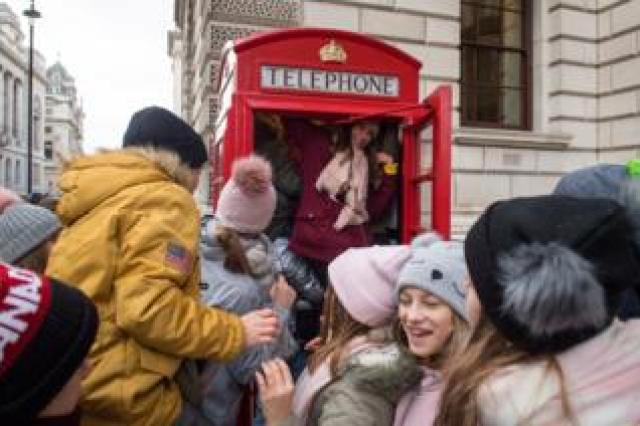 Polish tourists trying to see how many of them can fit into a red telephone box, in Westminster, London