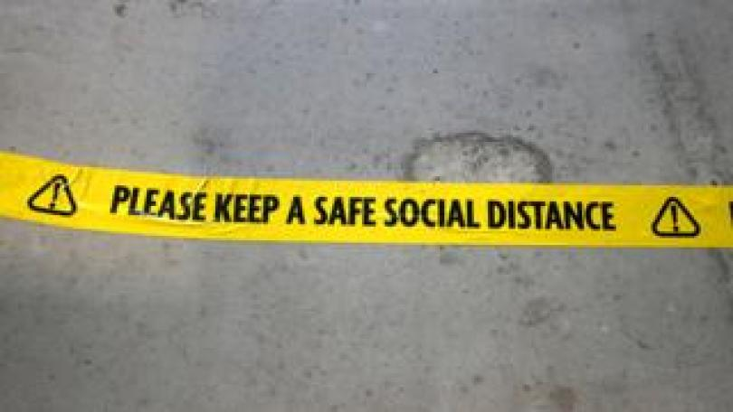 Floor sign reminding of need to social distance