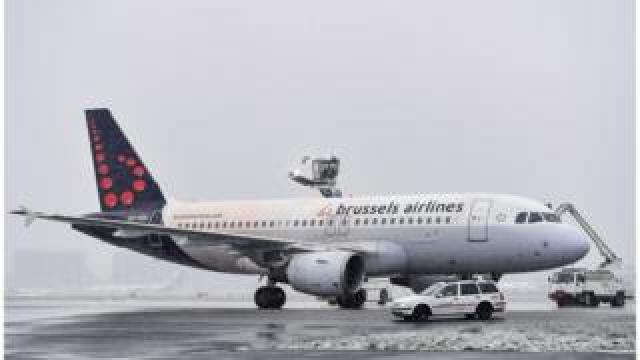 A Brussels airlines plane is seen on a snowy runway with vehicles de-icing it in this file photo