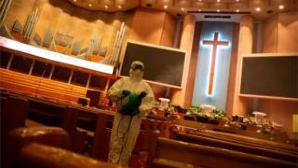 Worker disinfecting a church