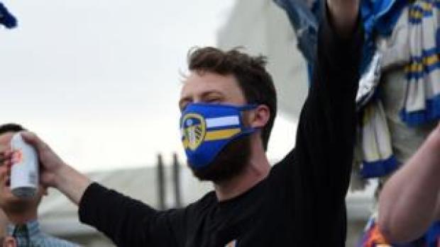 A fan wearing a Leeds United face mask