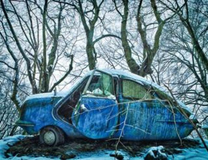 An abandoned blue car in an icy forest