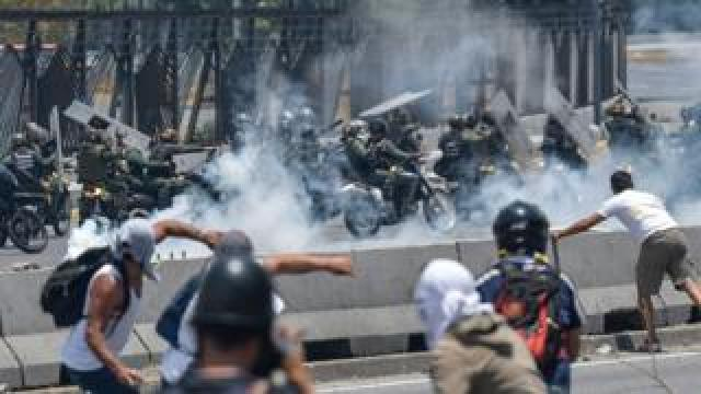 Anti-government protesters clash with security forces in the surroundings of La Carlota military base in Caracas