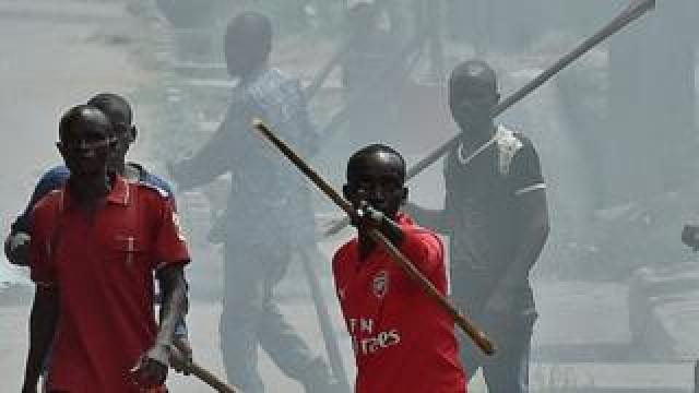 Members of the Imbonerakure, armed with sticks chase protestors opposed to the Burundian President's third term in the Kinama neighborhood of Bujumbura on May 25, 2015.