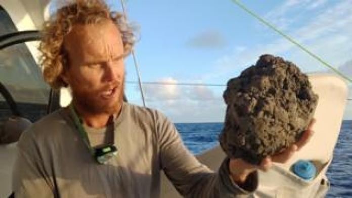 Michael Hoult holds a large pumice stone the size of his head