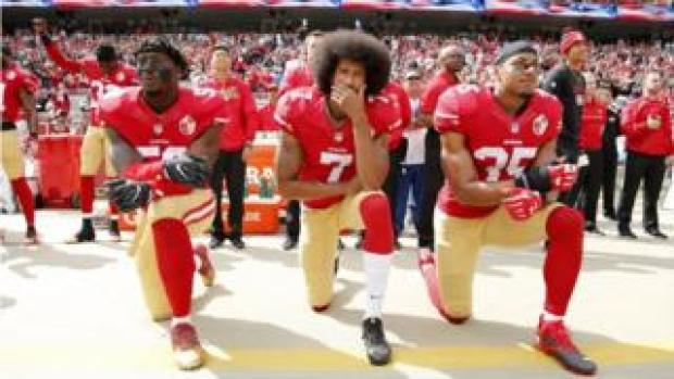 (L-R) Eli Harold, Colin Kaepernick and Eric Reid kneeling in protest during the American national anthem