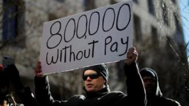 A protester holds a sign signifying hundreds of thousands of federal employees who won't receive salaries as a result of the partial government shutdown. Washington Jan 10 2019