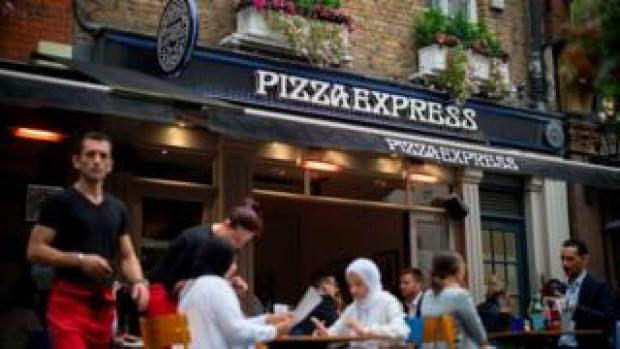 Customers sit outside Pizza Express restaurant in Central London