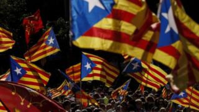 People wave 'Esteladas' (pro-independence Catalan flags) as they gather during a pro-independence demonstration, on September 11, 2017