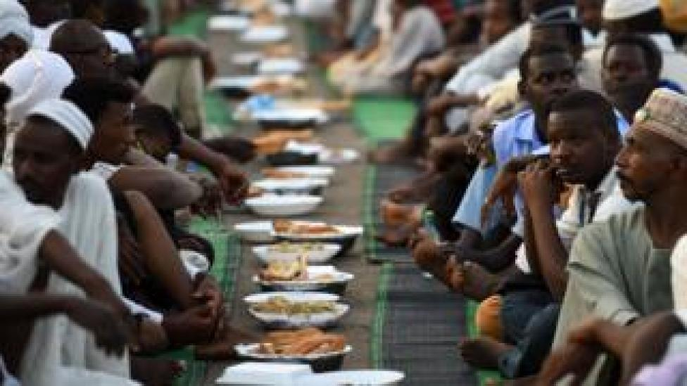 Sudanese men sit together as they are served Iftar at sunset during the Muslim holy month of Ramadan, at their protest outside the army headquarters in Sudan - 10 May 2019