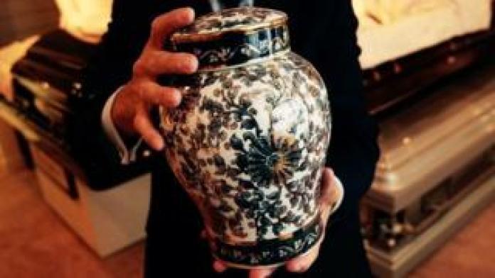 A man holds an ornate urn (FILE PHOTO)