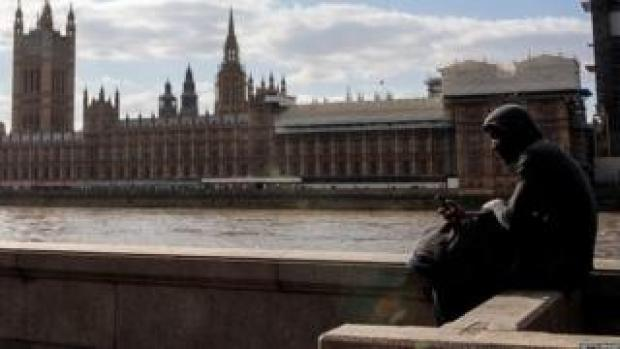 Man sits on the bank of the River Thames opposite the Houses of Parliament