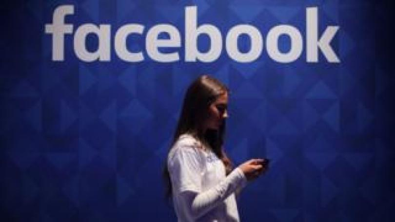 Woman using phone under a Facebook logo.