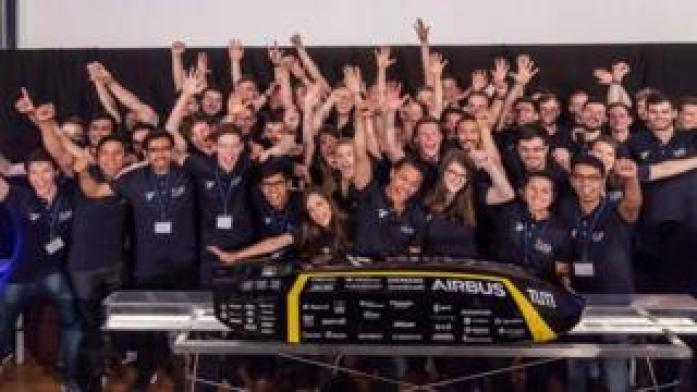 A Hyperloop test pod is surrounded by cheering students from the Munich University Team