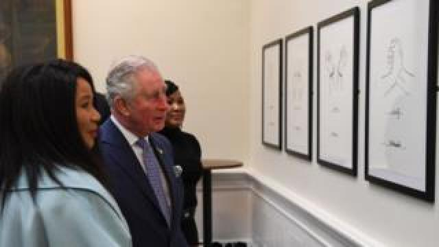 Prince Charles and Makaziwe Mandela look at drawings by Nelson Mandela on display in St Georges Hall in Liverpool