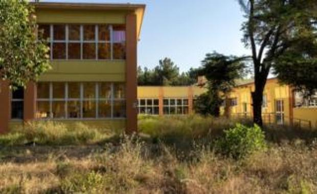 """One of the two schools shut down due to the high level of pollutants on the """"ecological hills"""" that were built between the schools and the plant"""