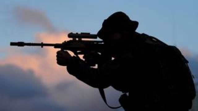 The silhouette of a soldier aiming a gun