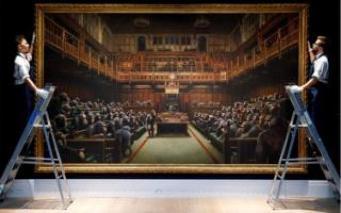 Gallery assistants pose with an artwork entitled Devolved Parliament by British artist Banksy
