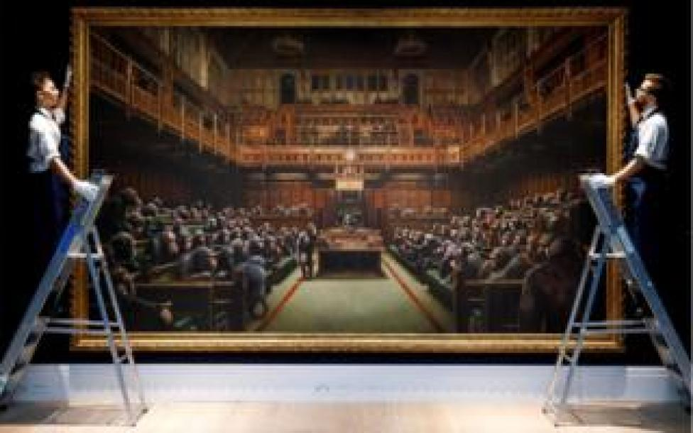 trump Gallery assistants pose with an artwork entitled Devolved Parliament by British artist Banksy