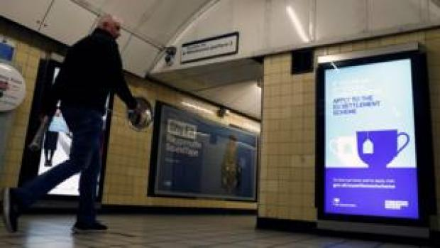 A man walks past a poster encouraging EU citizens to apply to the UK's post-Brexit settlement scheme