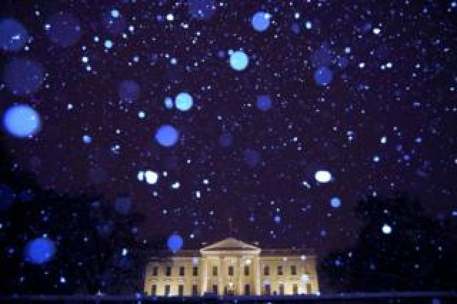 Snow is seen falling at night in front of the White House