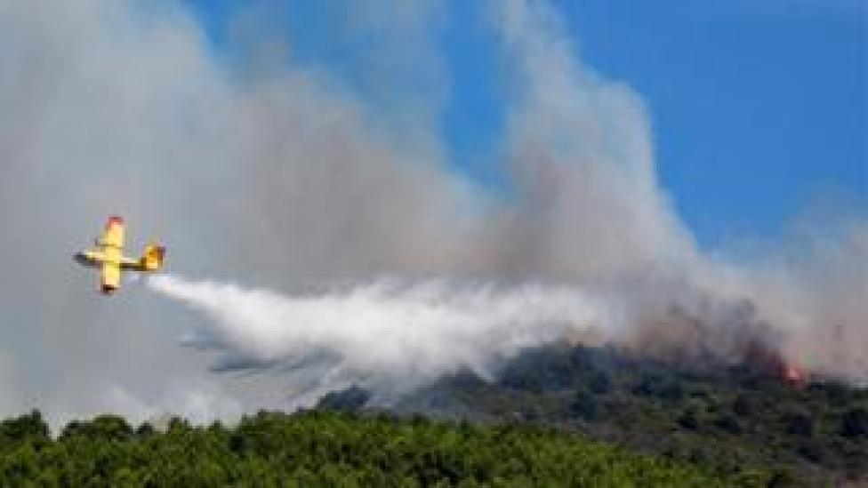 A yellow plane dumps water over a burning mountain forest in this file photo from the Tuscany region