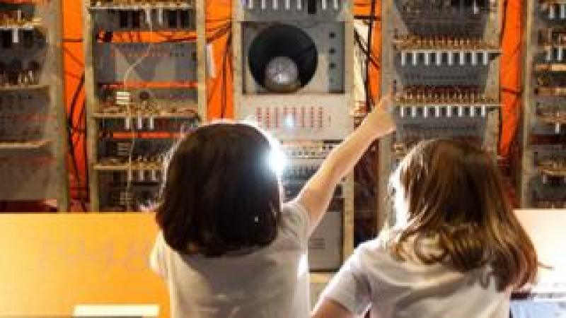 Children study a working replica of the machine