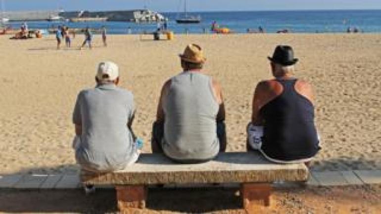 Männer, die heraus das Meer in Spanien betrachten