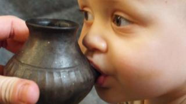 Modern day baby feeding from reconstructed vessel