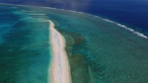A sand bar stretches forward into a shallow coral reef, with the open ocean beyond