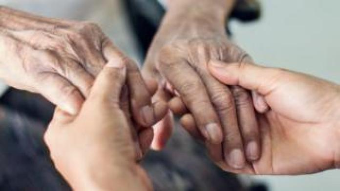 Caregiver holding the hands of the elderly person