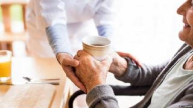 A health visitor handing a woman a cup of tea
