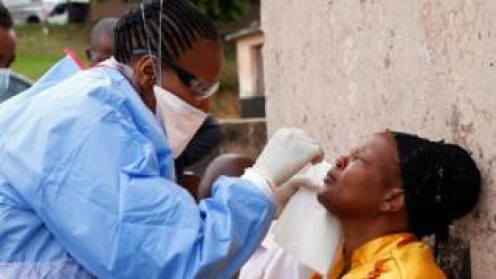 Health worker wearing protective suit takes swab from resident during door-to-door test