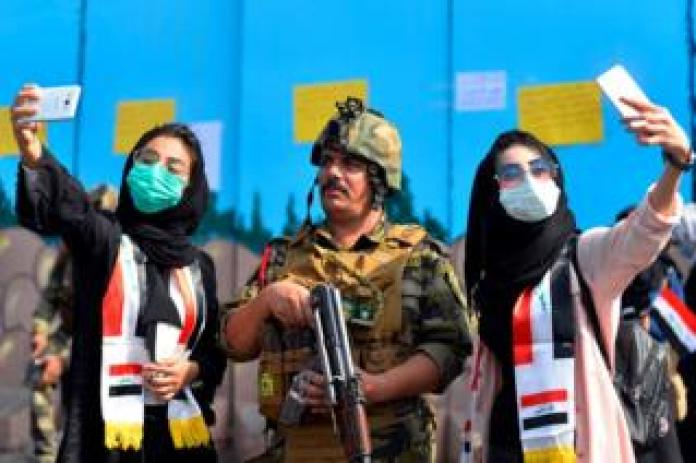 Iraqi students pose for selfies with a member of the security forces