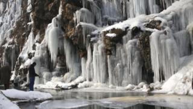 A man fishes near a frozen waterfall