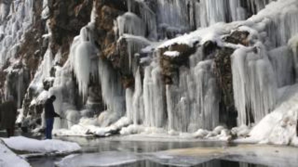 trump A man fishes near a frozen waterfall