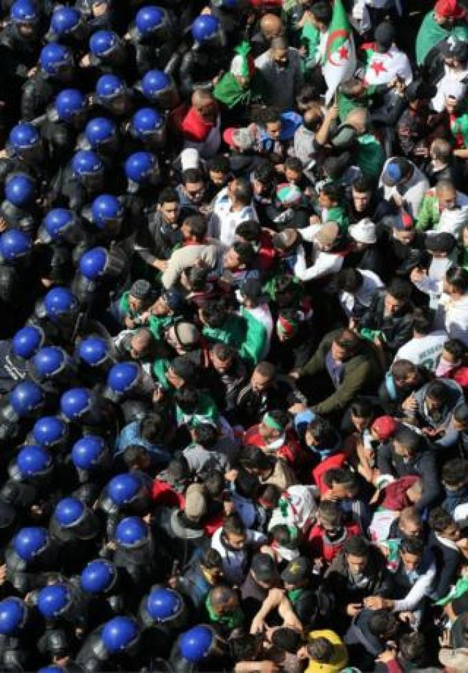 Algerian protester and blue-helmeted riot police are photographed clashing in an aerial shot taken in Algiers on 29 March 2019