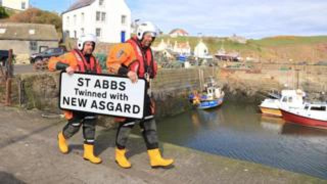 Lifeboat crew with sign