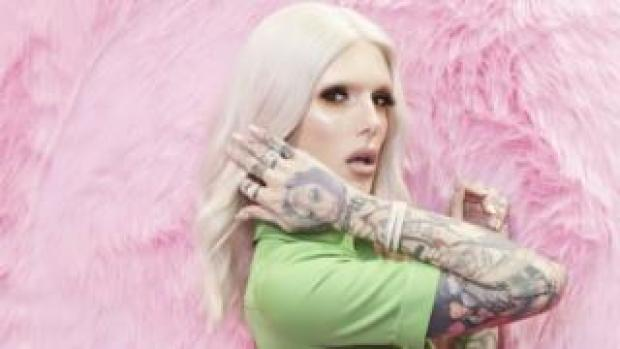 Jeffree Star standing against a pink fluffy background
