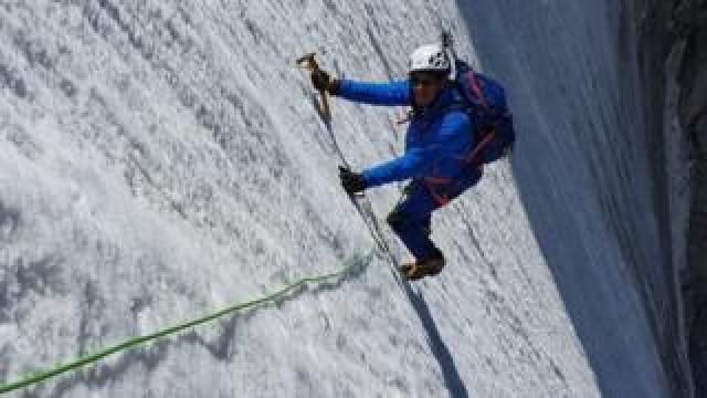Eric Woerth climbing the almost vertical mountain peak, fully equipped with chisel, ropes and a helmet.