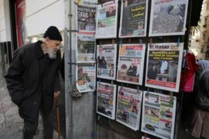 An elderly man in Algiers looks at the headlines of newspapers on display on 3 April, a day after Algeria's President Abdelaziz Bouteflika resigned