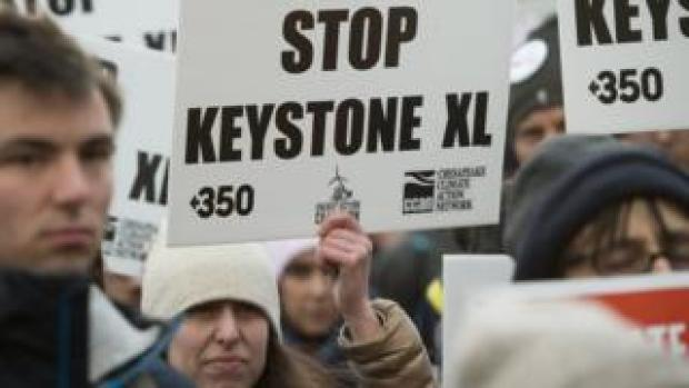 "A woman holds up a placard saying ""Stop Keystone XL"""