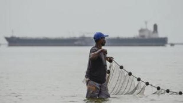 A fisherman hauls in his net in Lake Maracaibo in the Venezuelan city of Maracaibo, on 15 March 2019.