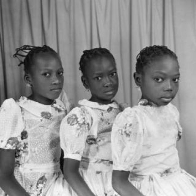 Three young girls wearing matching dresses, earrings and threaded hairstyles sit in a line and pose for the camera.