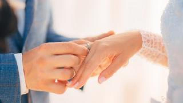 A groom puts a ring on a bride's finger