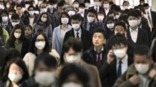 Office workers wearing protective masks to avoid infection from the coronavirus walk to their offices after taking overcrowded commuter trains, at a railway station in central Tokyo, Japan, 06 April 2020.